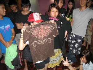 "Yi CHing in Vern's ""CHinese Character Cap"" and holding his brown tshirt. Zoe holding up Vern's ""Tulen Patrol"" tee and Julian wears Vern's skull bermudas."