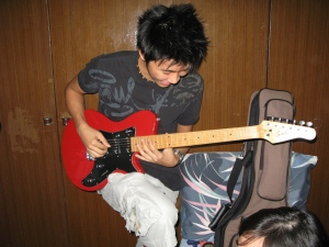 Jon ong strumming Vern's electric guitar