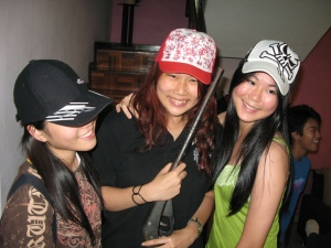 L to R: Yi Ching wearing Vern's cap, Zoe in the CHinese Character Cap and Chanelle in Vern's skull cap. Zoe holds Vern's toy shotgun from his 3 year old days.